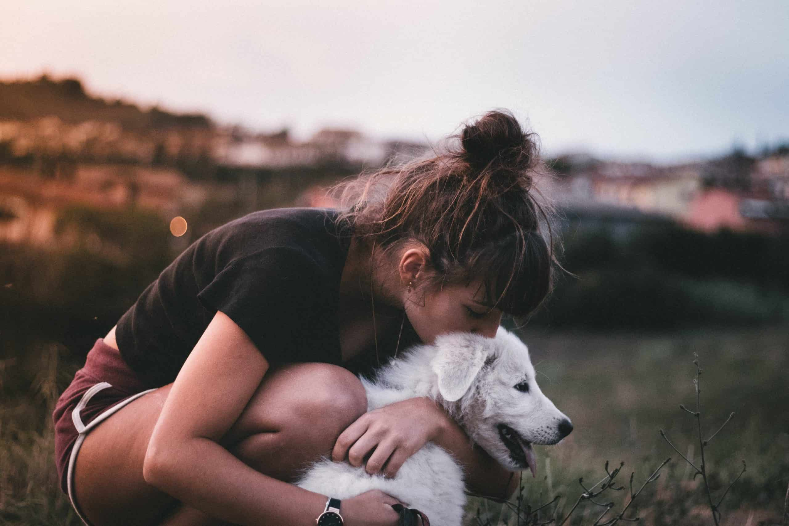 a girl hugging a dog